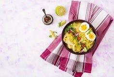 Sopa de macarronete com galinha, aipo e ovo em uma bacia em um fundo claro Imagens de Stock
