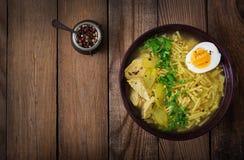 Sopa de macarronete com galinha, aipo e ovo em uma bacia em um fundo de madeira velho Imagens de Stock