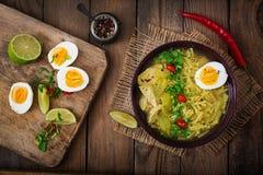 Sopa de macarronete com galinha, aipo e ovo em uma bacia em um fundo de madeira velho Imagem de Stock