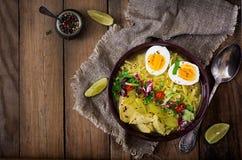Sopa de macarronete com galinha, aipo e ovo em uma bacia em um fundo de madeira velho Fotografia de Stock Royalty Free