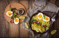 Sopa de macarronete com galinha, aipo e ovo em uma bacia em um fundo de madeira velho Foto de Stock