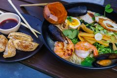 Sopa de macarronete com o marisco que inclui mexilhões, camarões, calamares, ovos e vegetais fotografia de stock royalty free