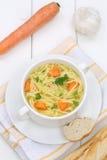 Sopa de macarronete no copo com macarronetes e baguette Imagens de Stock