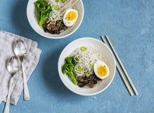 Sopa de macarronetes do arroz com brócolis, cogumelos e ovo cozido Alimento saudável do vegetariano Fotografia de Stock