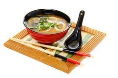 Sopa de Miso con la cebolla verde en el fondo blanco. Fotografía de archivo