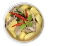 Sopa de patata con cerdo y chiles calientes cortados en el fondo blanco imagen de archivo