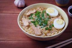 Sopa de pollo china Cocinado en un wok Fondo de madera imagenes de archivo