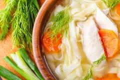Sopa de pollo hecha en casa con los tallarines con las zanahorias y las hierbas en un cuenco en un tablero de madera Visión super Imagenes de archivo