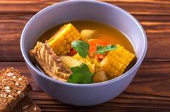 Sopa de Puchero com milho e salsa na tabela de madeira Fotos de Stock