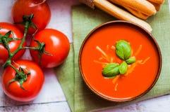 Sopa de Tomatoe com varas de pão e manjericão no fundo de madeira Fotos de Stock Royalty Free