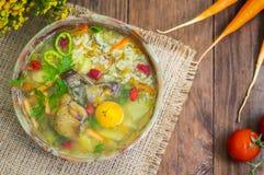 Sopa del arroz con los ombligos del pollo y la yema de huevo Fondo rústico de madera Visión superior Primer imagen de archivo