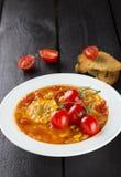 Sopa del maíz con los tomates de cereza en la placa blanca Imagen de archivo