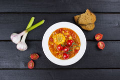 Sopa del maíz con los tomates de cereza en la placa blanca en backgrou de madera Fotografía de archivo