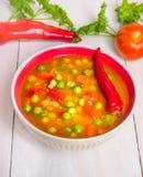 Sopa del minestrone en cuenco rojo Foto de archivo libre de regalías