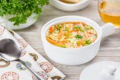 Sopa del orzo del pollo en un cántaro blanco en fondo de madera Sopa italiana con las pastas del orzo Imagenes de archivo