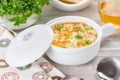 Sopa del orzo del pollo en un cántaro blanco en fondo de madera Sopa italiana con las pastas del orzo Fotos de archivo libres de regalías