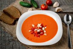 Sopa del tomate de Gazpacho en una cuchara blanca del cuenco en una toalla en el fondo de tableros de madera Imagen de archivo libre de regalías