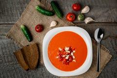 Sopa del tomate de Gazpacho en una cuchara blanca del cuenco en una toalla en el fondo de tableros de madera Fotografía de archivo