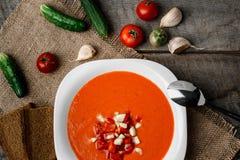 Sopa del tomate de Gazpacho en una cuchara blanca del cuenco en una toalla en el fondo de tableros de madera Imagenes de archivo