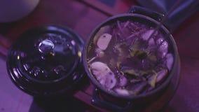 Sopa deliciosa con las setas y los tallarines en el cuenco del metal con una tapa en la tabla en el club nocturno en luz azul almacen de video