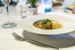 Sopa deliciosa de la bola de masa hervida del tocino de Tyrolian en una tabla con una bifurcación imagen de archivo