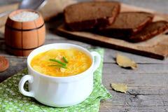 Sopa deliciosa do arroz com galinha, batatas, as cebolas verdes e as cenouras em uma bacia Fatias do pão, guardanapo verde Fotos de Stock