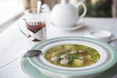 Sopa dietética con las albóndigas del pollo y tallos del apio e hierbas y patatas aromáticas imagenes de archivo