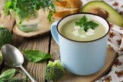 Sopa do copo azul keramtcheskoy dos brócolis e do abacate no fundo de madeira velho da tabela Imagens de Stock Royalty Free
