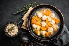 Sopa do legume fresco com almôndegas e cevada de pérola na bacia no fundo preto fotos de stock