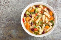 Sopa do minestrone Sopa vegetal com tomate, aipo, a cenoura, o abobrinha, a cebola, pimento, os feijões e massa frescos Imagem de Stock