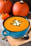 Sopa do outono na bacia azul com as abóboras no fundo Fotos de Stock Royalty Free