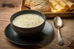 Sopa do queijo em uma placa preta no fundo de madeira rústico Fotografia de Stock Royalty Free