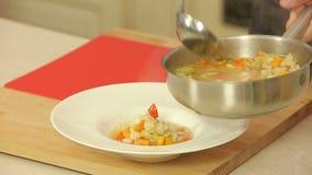 Sopa do serviço com feijões e vegetais vídeos de arquivo