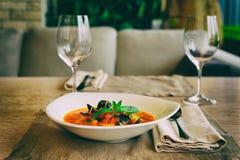 Sopa dos peixes do tomate na tabela do restaurante, tonificada fotografia de stock