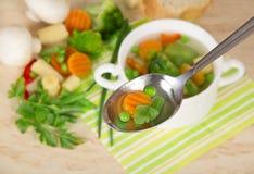 Sopa em uma colher e em um grupo de vegetais Foto de Stock