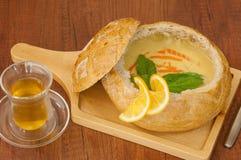 Sopa en un cuenco del pan en el tablero foto de archivo libre de regalías