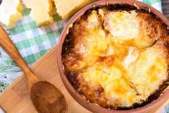 Sopa francesa en un pote de arcilla, receta auténtica, cuchara de madera en una tabla de cortar en una tabla rústica vieja, prime Imagen de archivo