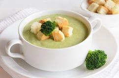Sopa fresca de la crema del bróculi servida con los cuscurrones foto de archivo