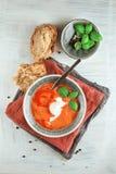 Sopa fresca del tomate en un cuenco con los tomates y albahaca en una tabla de cocina blanca Fotos de archivo