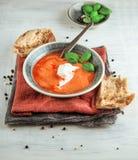 Sopa fresca del tomate en un cuenco con los tomates y albahaca en una tabla de cocina blanca Imagen de archivo libre de regalías