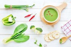 Sopa, galletas y verduras verdes en una tabla blanca Imágenes de archivo libres de regalías