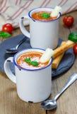 Sopa hecha en casa de la albahaca del tomate en la taza, servida con el palillo del queso de la mozzarella Fotografía de archivo