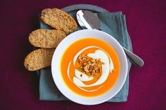 Sopa hecha en casa de la patata dulce y de la zanahoria con los chiles y el jengibre adornados por la crema agria y el cacahuete  Imagen de archivo libre de regalías