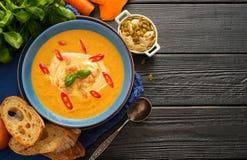 Sopa hecha en casa deliciosa de la calabaza con el pasto de las gambas, del chile y de la albahaca Fotos de archivo