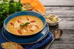 Sopa hecha en casa deliciosa de la calabaza con el pasto de las gambas, del chile y de la albahaca Imágenes de archivo libres de regalías