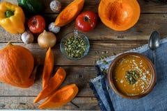 Sopa hecha en casa tradicional de la calabaza con los seads, la crema y las verduras en la tabla de madera rústica Imagen de archivo