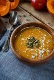 Sopa hecha en casa tradicional de la calabaza con los seads, la crema y las verduras en la tabla de madera rústica Foto de archivo libre de regalías