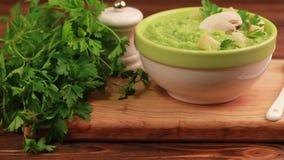 Sopa hecha puré sabrosa fresca del bróculi en cuenco de la arcilla con los ingredientes en tabla de cortar almacen de metraje de vídeo