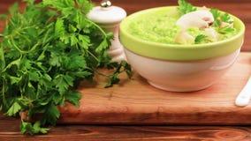 Sopa hecha puré sabrosa fresca del bróculi en cuenco de la arcilla con los ingredientes en tabla de cortar metrajes