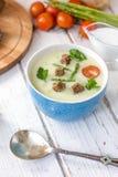 Sopa hermosa de la crema del espárrago con pan tostado en la tabla de madera blanca Imagenes de archivo